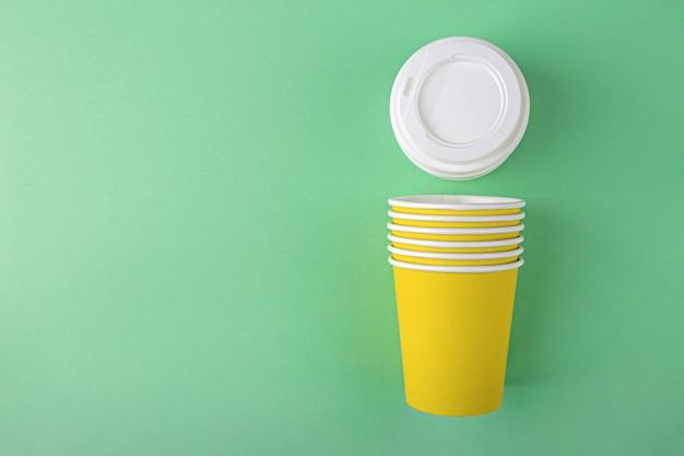 Gobelets Jetables En Papier Jaune Avec Couvercles En Plastique Pour Café Ou Thé à Emporter Sur Fond Vert Avec Espace Copie Photo Premium