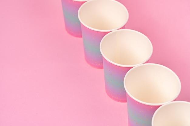 Gobelets En Papier Jetables Roses D'affilée Sur Fond Rose Photo Premium