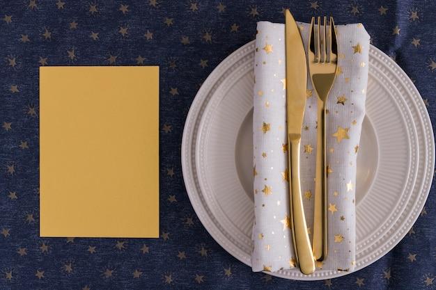 Gold fourchette et couteau sur assiette avec du papier Photo gratuit
