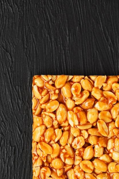 Golden bolets kozinaki à partir de barres énergétiques de haricots cacahuètes grillées. fond de texture noir, vue de dessus Photo Premium
