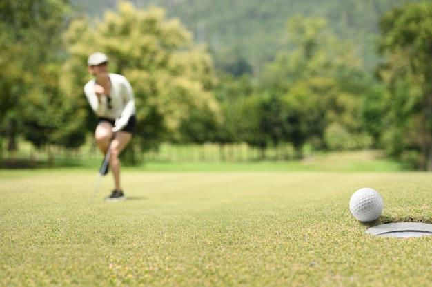 Golfeur femme acclamant après une balle de golf sur un green de golf Photo Premium