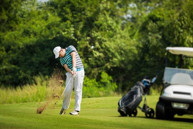 Golfeur frapper la balle avec force. la répartition de l'herbe le flou du golf Photo Premium