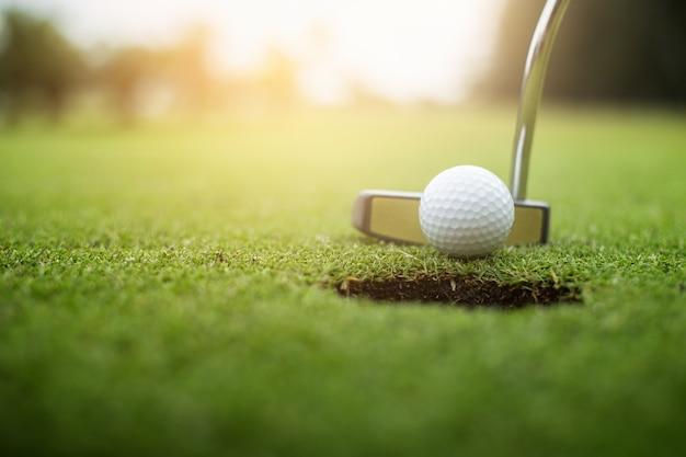 Golfeur mettant la balle de golf approche du trou de golf sur le golf vert Photo Premium
