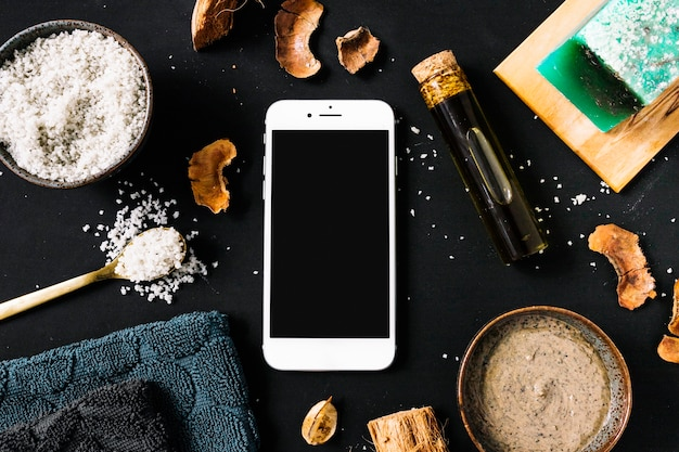 Gommage du corps; coquille séchée; huile essentielle; barre de savon; serviette et smartphone sur fond noir Photo gratuit