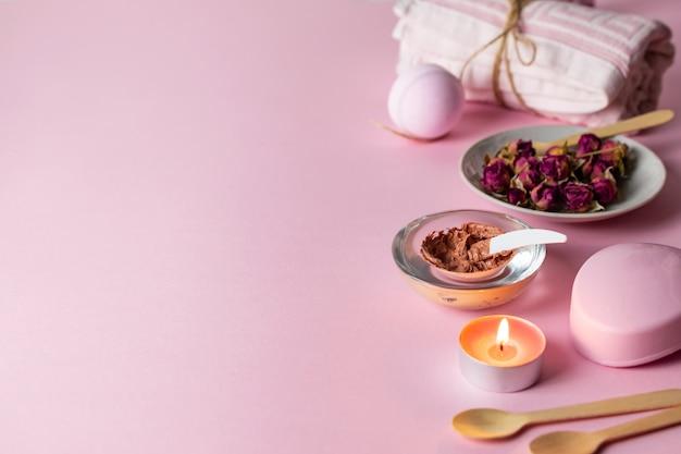 Gommage Et Soins De La Peau à La Rose Faits Maison Avec Des Ingrédients Naturels Sur Fond Rose Avec Des Serviettes, Des Bougies Et Du Savon. Photo Premium