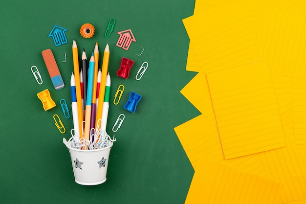 Gomme à effacer pour stylo trombone papeterie crayons dans un seau blanc. nature morte sur fond de commission scolaire verte. espace de copie plat laïque vue de dessus concept education Photo Premium