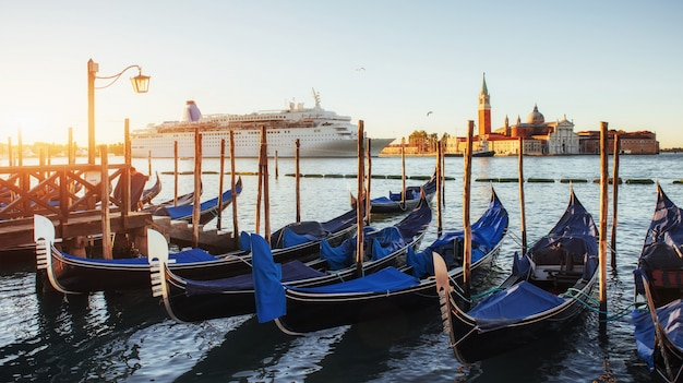 Gondoles à venise - coucher du soleil avec l'église san giorgio maggiore. venise, italie Photo Premium