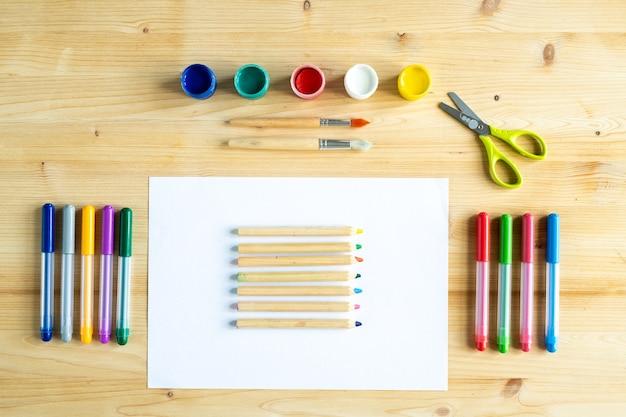 Gouaches Colorées, Pinceaux, Ciseaux, Crayons De Couleur Sur Une Feuille De Papier Vierge Et Surligneurs Sur Table En Bois Photo Premium