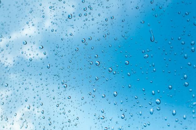 Gouttelettes d'eau sur le verre des fenêtres contre le ciel bleu, saison des pluies Photo Premium