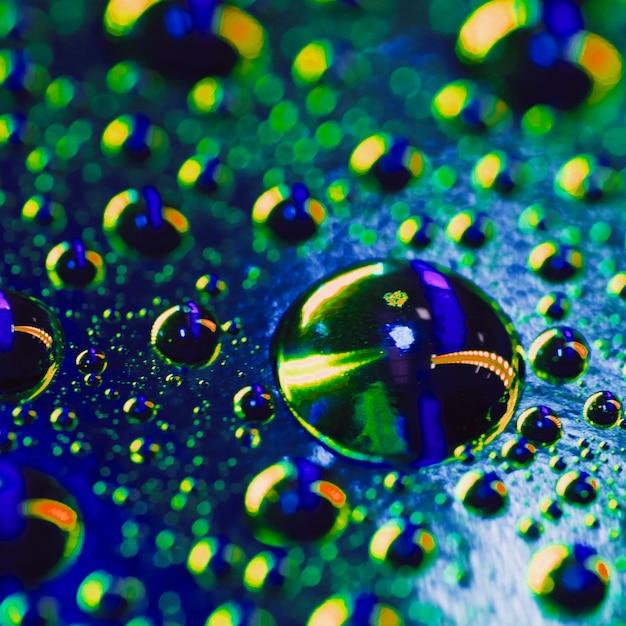Gouttes d'eau sur la surface avec un reflet coloré brillant Photo gratuit