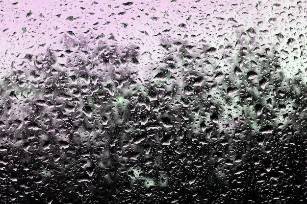 Gouttes d'eau sur le verre contre le ciel et les arbres. Photo Premium