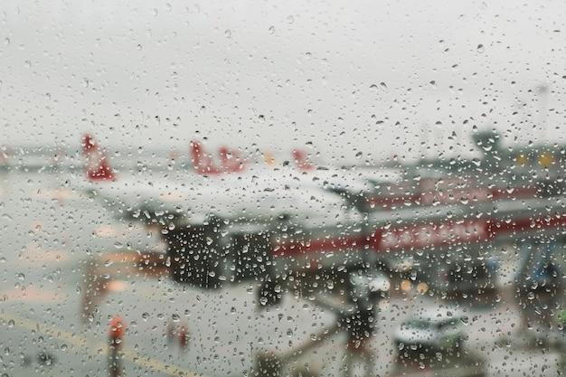 Gouttes de pluie sur la fenêtre de l'aéroport Photo Premium