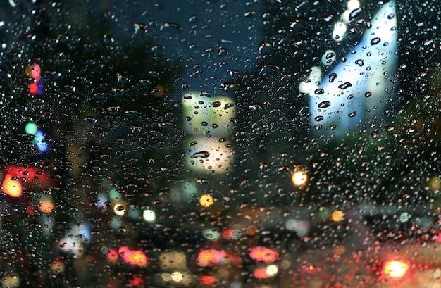 Gouttes de pluie sur le pare-brise de la voiture avec embouteillage flou dans la rue urbaine la nuit Photo Premium