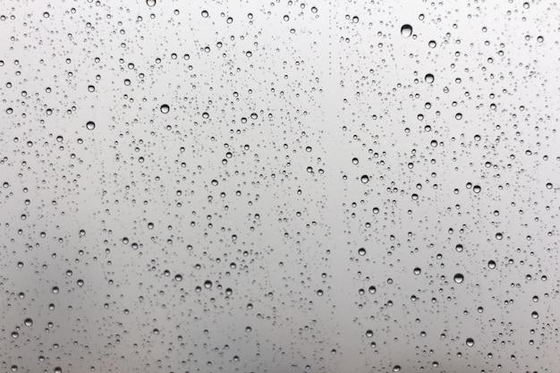 Gouttes de pluie sur la surface des lunettes de fenêtre avec fond nuageux Photo Premium