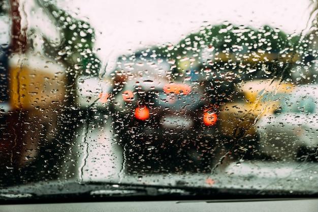 Gouttes de pluie sur le verre de la voiture avec embouteillage flou sur la route en arrière-plan à kolkata, en inde. Photo Premium