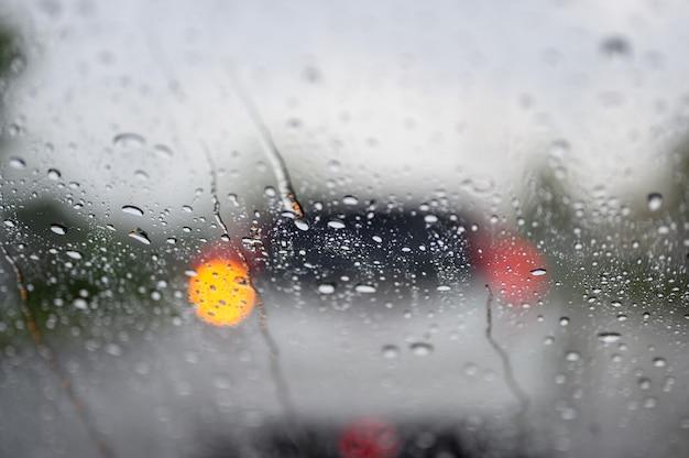 Gouttes de pluie sur la vitre de la voiture lors d'embouteillages Photo Premium