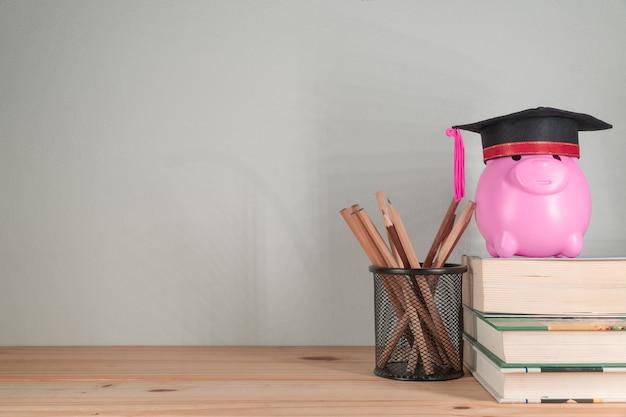 Graduation cap avec la tirelire sur les livres. Photo Premium