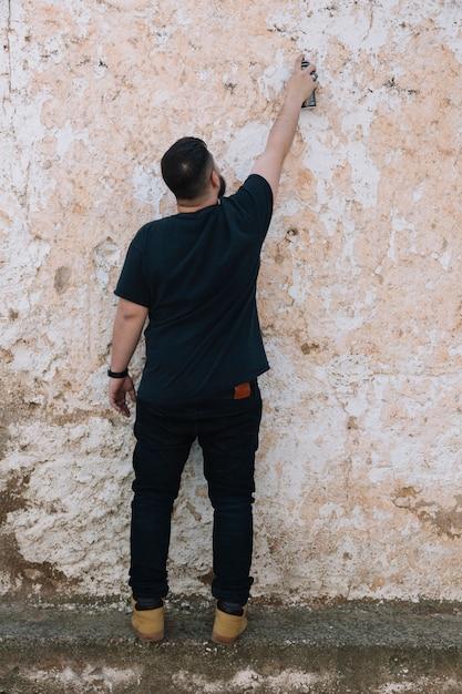 Graffiti artiste peinture avec aérosol sur le mur sale Photo gratuit