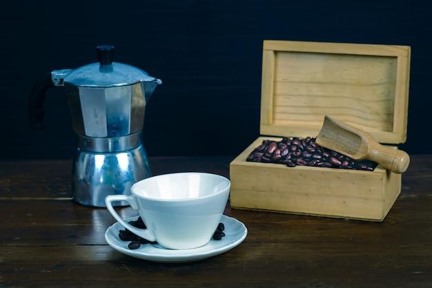 Grain de café dans une tasse à café blanche sur le vieux fond de bois. Photo Premium