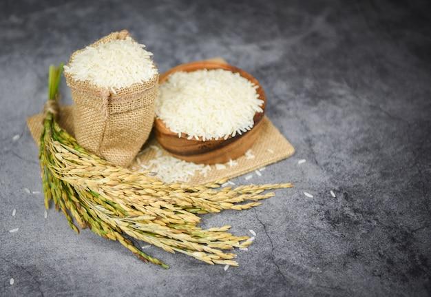 Grain De Riz Au Jasmin Cru Avec Oreille De Produits Agricoles De Paddy Pour La Nourriture En Asie - Riz Thaï Blanc Sur Bol Et Fond De Sac Photo Premium