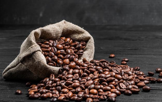 Graines de café biologique se dispersant à partir d'un sac sur la surface en bois sombre. grains de café frais près du sac brun clair isolé. fermer Photo Premium