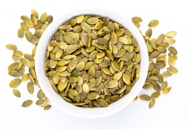 Graines de citrouille (graines pelées) dans un bol blanc (collection de noix diverses). isolé Photo Premium