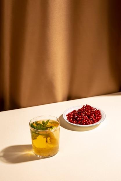 Graines de grenade rouge vif avec boisson cocktail sur tableau blanc Photo gratuit
