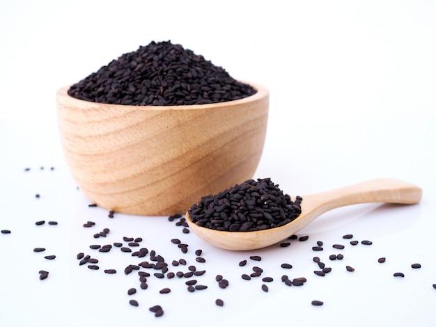 Graines De Sésame Noir Dans Une Cuillère En Bois Isolé Sur Une Surface Blanche. Photo Premium