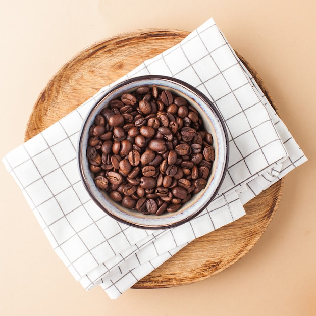 Grains De Café Arabica Dans Un Bol En Céramique Sur Un Plateau En Bois Sur Un Fond Marron. Photo Carrée Pour Les Cafés Et Les Cafés. Photo Premium