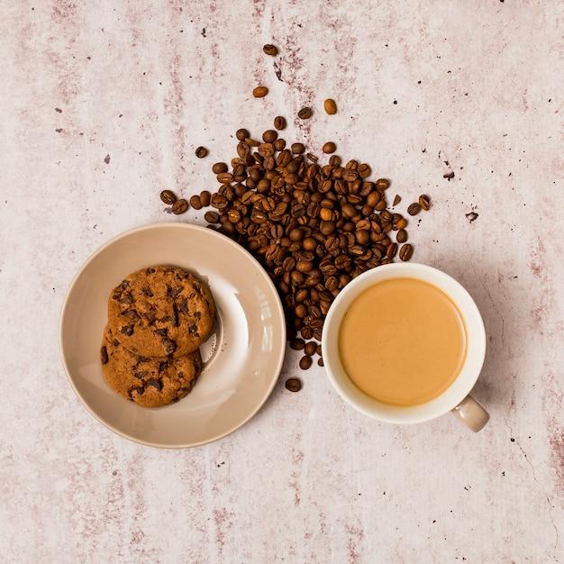Grains de café, biscuits et tasse à café Photo gratuit