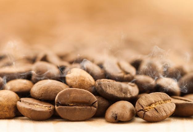 Grains De Café Brun Avec De La Vapeur De Fumée Blanche Sur Fond De Planche De Bois Texturé Jaune Se Bouchent. Photo Premium