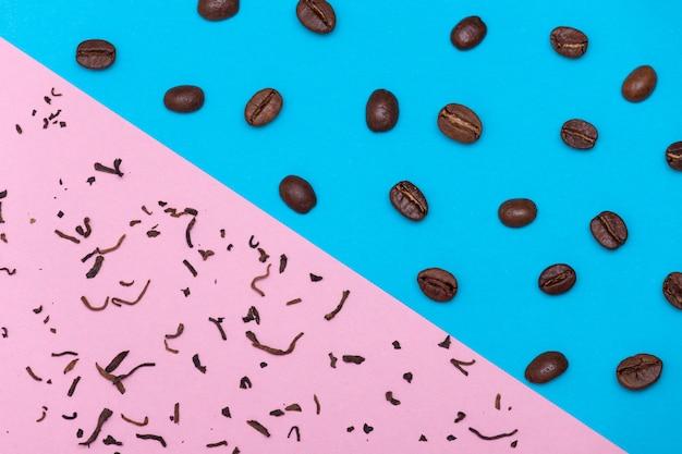 Grains de café bruns sur fond bleu et thé sec sur fond rose. concept de thé ou de café. Photo Premium