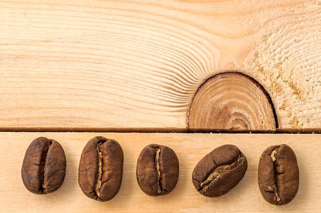 Grains de café bruns sur fond de planche de bois texturé jaune se bouchent. Photo Premium