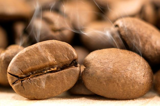 Grains de café bruns avec de la vapeur de fumée blanche sur jaune texturé. Photo Premium