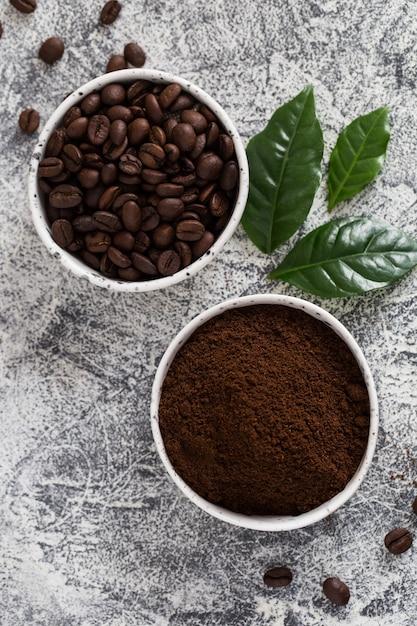 Grains de café et café moulu dans des bols avec feuille de caféier à la lumière. Photo Premium