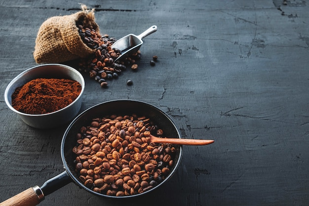 Grains de café et café en poudre sur un fond en bois noir Photo Premium