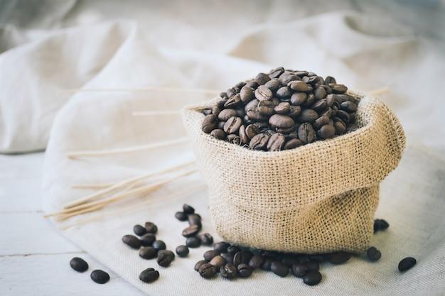 Grains de café dans un sac de jute et bâton sur fond de bois blanc Photo Premium