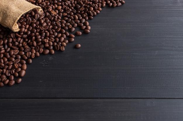 Grains de café dans un sac de jute sur vieux bois avec flou artistique et lumière en arrière-plan Photo Premium