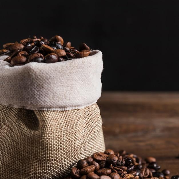 Grains de café dans un sac et sur la table Photo gratuit