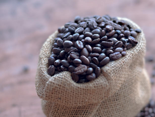 Grains de café dans le sac sur la table Photo Premium