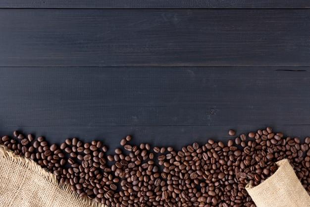 Grains de café dans un sac en toile de jute sur fond en bois ancien. vue de dessus Photo Premium