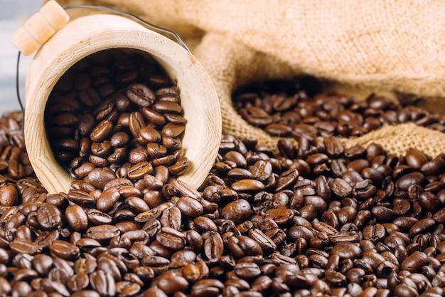 Grains de café dans un seau décoratif sur des grains de café Photo Premium