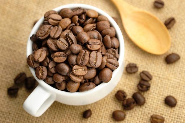 Grains de café dans la tasse blanche placée sur un sac. Photo Premium