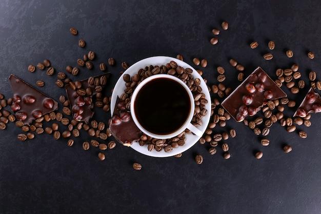 Grains de café épars, une tasse et du chocolat noir sur une table en pierre noire. espace de copie. Photo Premium