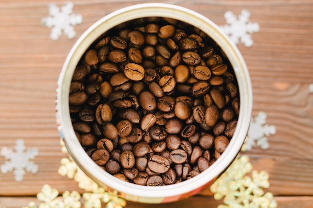 Grains de café en étain sur une table en bois avec des décorations Photo Premium