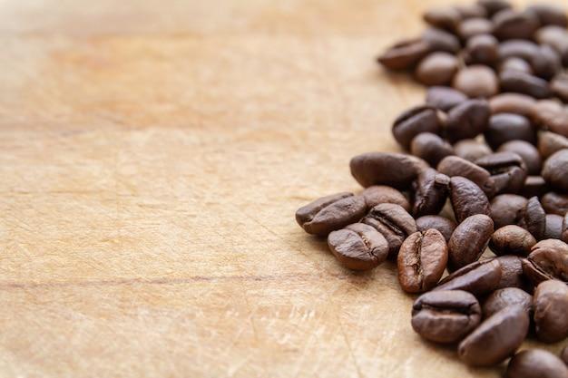 Grains de café sur fond en bois marron grunge. gros plan, mise au point sélective, fond Photo Premium