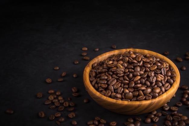 Grains De Café Frits Dans Un Bol En Bois Sur Pierre Noire Photo Premium