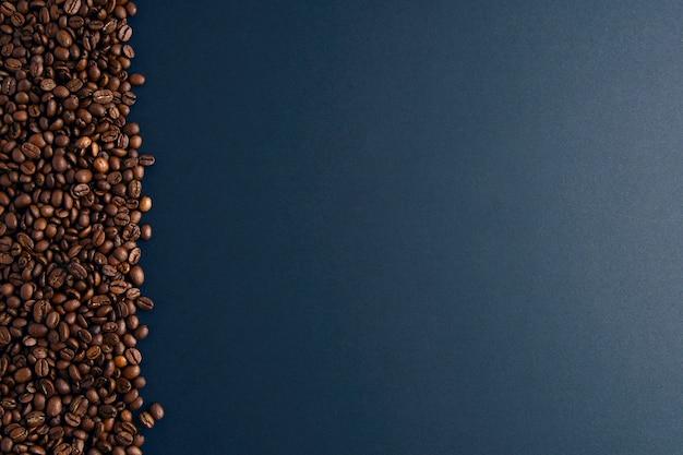Grains de café à gauche sur fond noir Photo Premium