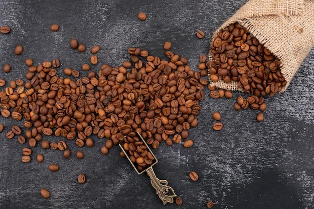Grains De Café En Grains Dans Une Cuillère En Métal Et Un Sac Sur Une Surface Sombre Photo gratuit