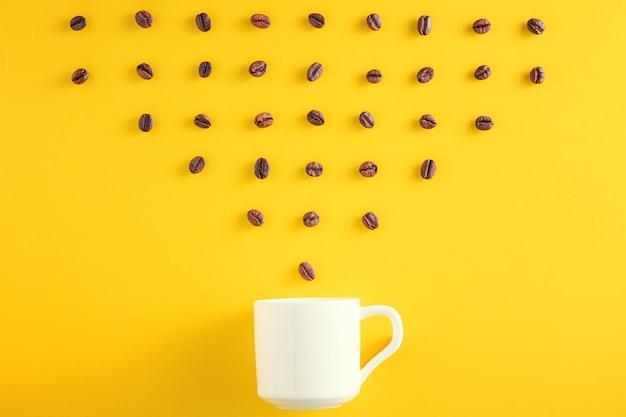 Grains de café en ligne et tasse de café sur fond jaune Photo Premium
